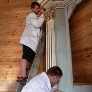 Ant kopėčių darbuojasi aukščiausios kvalifikacinės kategorijos polichromuoto medžio restauratorius Rolandas Vičys, įsitaisęs žemiau – Linas Lukoševičius